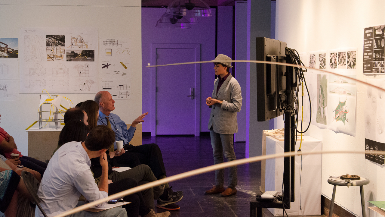 Misha Semenov engages with University Architect Ron McCoy during Hayley Eber's spring 2014 JIW Studio review.